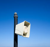 White loudspeaker. Isolated in nice blue background tied to metal column Royalty Free Stock Photos