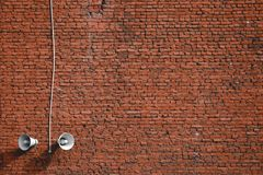 White loudspeakers on a red brick wall background royalty free stock photography