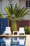 White lounge chair at the pool side. Swimming pool with lounge chair stock photo