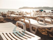 White loungers on a beach at sunset. Golden our in the mediterranean stock photos