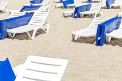 White loungers with blue mattresses on a public beach. Horizontal stock photography
