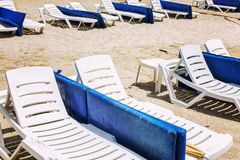 White loungers with blue mattresses on a public sandy beach. Horizontal royalty free stock image