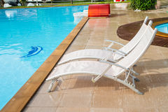 White lounges next to a swimming pool Royalty Free Stock Photos