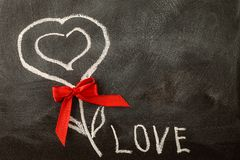 White LOVE greeting message with Heart symbol on blackboard. Valentine`s Day background stock photo