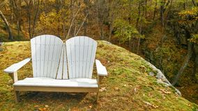 Adirondack Love Seat Chair on a Rock Ledge. A white love seat, wooden, adirondack chair sitting on a moss covered rock ledge overlooking a scenic drop off stock images