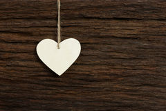 White Love Valentine's heart hanging on wooden texture backgroun Royalty Free Stock Images