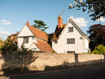 A white lovely cottage house in soft light and a brick wall and. Road in dedham; UK Royalty Free Stock Photos