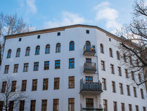 White Low Rise Building with Small Balconies. Architectural Exterior Corner View of Generic White Building with Residential Balconies Surrounded by Bare Trees Stock Image