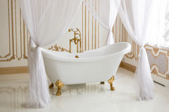 White luxurious bath with golden legs at bathroom. Beautiful view of white luxurious bath with golden legs at bathroom Royalty Free Stock Photo