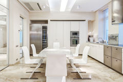 White luxury kitchen. In a modern house with stone floors and white furniture Stock Image