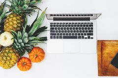 White Macbook Near Pineapple and Pumpkin Royalty Free Stock Photos