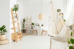 White macrame hammock. In spacious dining room interior with decorations on wooden ladder and rattan lamp above the table Stock Photo