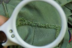 white magnifier enlarges a piece of green cloth with a seam stock photos