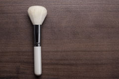 White make-up brush on brown table. White make-up brush on brown wooden table Royalty Free Stock Photography
