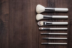White make-up brushes on wooden table Stock Images
