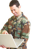 White male in army uniform on lap top smiling Royalty Free Stock Photos