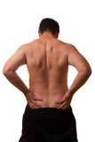White Male with Back Pain - Bare Torso. Rear torso of caucasian male 30 stretching bare back, head hung low Royalty Free Stock Photo