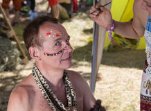 White male dressed in African aborigines. With a tambourine at the festival of colors Royalty Free Stock Images