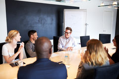 White male executive receiving applause from colleagues. During a meeting stock images