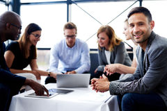 White male executive smiling at camera during meeting. White male executive sitting and smiling at camera during a meeting with colleagues Royalty Free Stock Photos