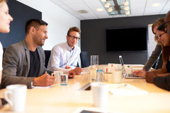 White male executive smiling at camera in work meeting. White male executive smiling at camera during a meeting with colleagues Royalty Free Stock Photos