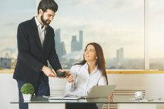 White male and female working together. Portrait of white male and female working together and serving coffee at modern office desk. Meeting, secretary, teamwork Stock Images