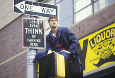 White male in New York sits on sign Stock Image