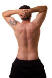 White Male Stretches Back. Rear torso of caucasian male 30 stretching bare back. Tattoo on left shoulder with hands behind head Royalty Free Stock Image