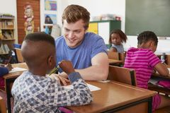 White male teacher helping elementary school boy in class Stock Image
