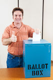 White Male Voter. White male mid adult voter dropping his ballot in the box and giving a thumbs up royalty free stock images