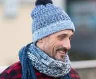 Portrait of smiling white guy on street. White male in winter knitted hat and scarf. Bearded man in blue-white hat and red jacket stock photos