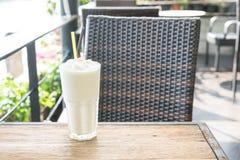 White malt milkshake. On wood table Stock Photos