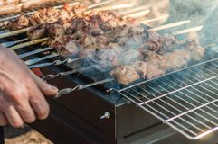 Cooking shish kebab on a charcoal grill. White man cooking shish kebab on a barbecue grill over charcoal Royalty Free Stock Image