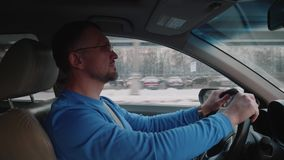 White man drives in afternoon with busy city on background. End of busy day stock video
