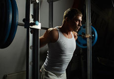 White man give barbell in gym power rack. Young sportsman put barbell on his shoulder in gym power rack stock images
