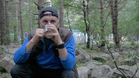 A white man with a gray beard, traveling in the forest. He rests and drinks tea. HD stock video