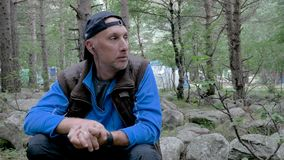 A white man with a gray beard travels through the forest. He rests and listens to music through headphones. HD stock video footage