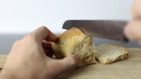 White man hands cutting a loaf of bread with a bread knife stock video