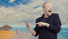 A white man looks at the smartphone and feels shock and surprise with an overly facial expression. A man in a black jacket on the beach holds a smartphone in Stock Image