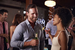 White man and mixed race woman talking at a party, side view stock photos