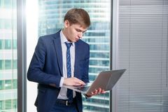White man in office with laptop on city background. Business Technology finance concept stock photo