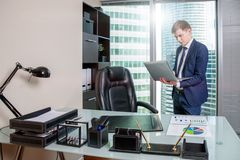 White man in office with laptop on city background. Business Technology finance concept royalty free stock photography