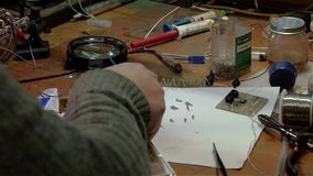 White man repairing a broken electronic led lamp in old workshop stock video footage