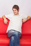 White man sitting on a red couch. In studio Royalty Free Stock Photography