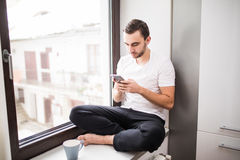 White man sitting on a windowsill in a home environment holding a phone and reading messages at home Stock Photos