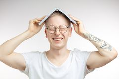 White man smile and hides his face behind a book. Studio portrait. Cute blonde albino guy, collegue man in white plain t-shirt smiling keeping book over head stock photography