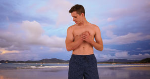 White man in swim shorts standing on beach. Royalty Free Stock Images