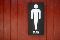 Male toilet signs Made of wood. White man toilet sign on red wooden background Royalty Free Stock Photos