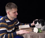 White manly man next to the table where the cat sits, lies a book and a rose flower stock photo