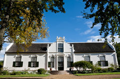 White manor house on a winefarm. Framed with autumn color leaves against a blue sky in the Western Cape, South Africa Stock Images